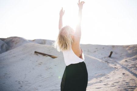 Woman raises her hands to the sun in happiness