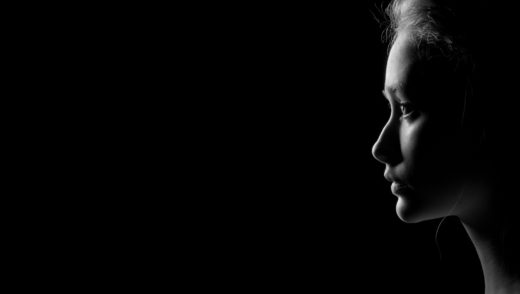 profile of young pensive woman with red hairs on black background with copyspace, monochrome