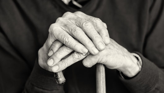 old man's hands leaning on can