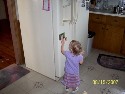 small girl in front of refrigerator