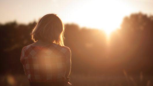 girl in field looking towards sunrise