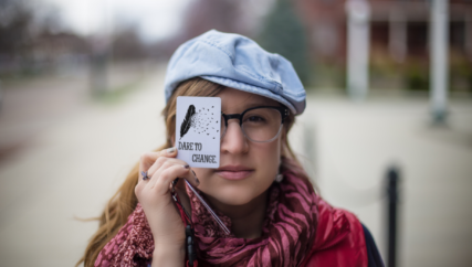 Girl holding card that reads Dare to Change