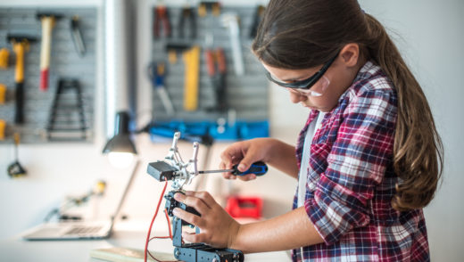 Young girl doing some robotics in a workshop.