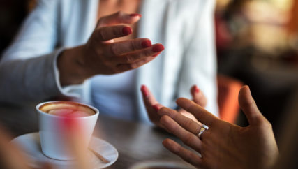 Close up of unrecognizable businesswomen gesturing while discussing in a cafe.