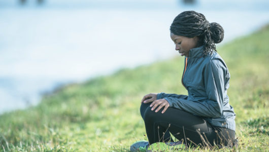 female practicing meditation outdoors