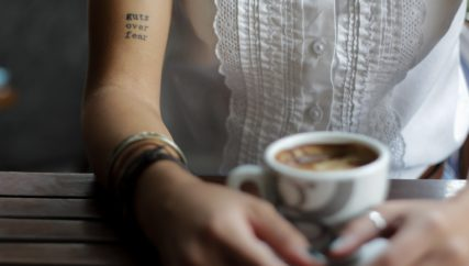 woman with coffee and tatoo that reads guts over fear