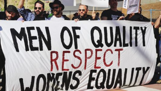 men marching with sign reading Men of Quality Respect Womens Equality