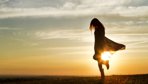 girl in silhouette walking through field