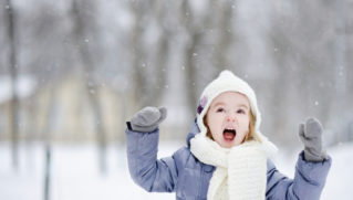 Little girl screaming outdoors on clear winter day