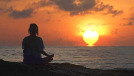 Woman meditating in lotus position. Sunset