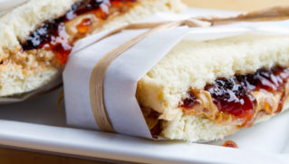 PB&J sandwich wrapped in parchment. Served on a white plate.