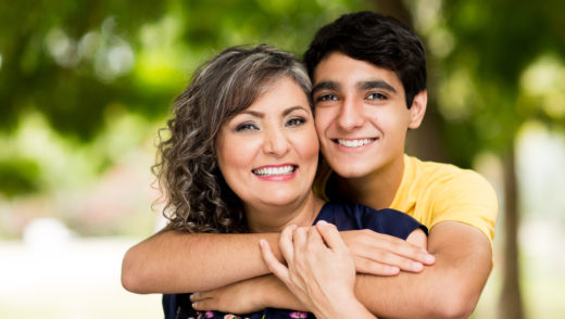 Loving portrait of mother and son smiling in a park