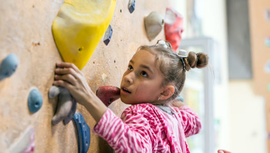 Junior Climber Girl hanging on holds on climbing wall of indoor gym
