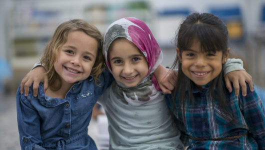 Little Muslim girl wearing a hijab is enjoying the day at school with her friends.