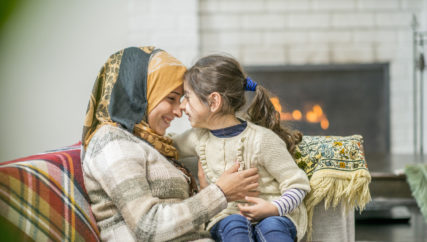 A Muslim mother is smiling while sitting on the couch, with her daughter in her lap. She is wearing a head scarf. They are smiling while their faces are close to each other.