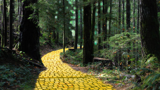 yellow brick road through woods with Emerald City peeking trhough trees in background