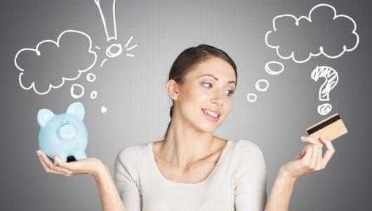 woman deciding between piggy bank and credit card