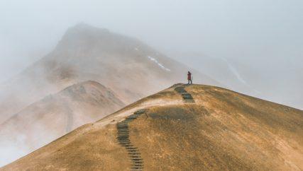person walking up trail on hillside