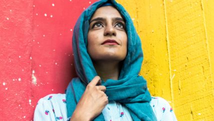 woman in head scarf standing in front of a brightly colored wall