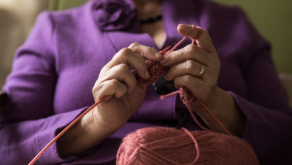 Close up of unrecognizable old woman knitting with wool.