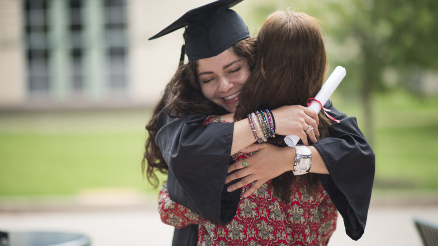 Female college student hugging her mother on graduation date