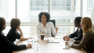 Black female boss leading corporate multiracial team meeting talking to diverse businesspeople, african american woman executive discussing project plan at group multi-ethnic briefing in boardroom