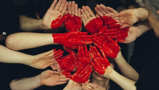 hands arranged and painted to display a red heart