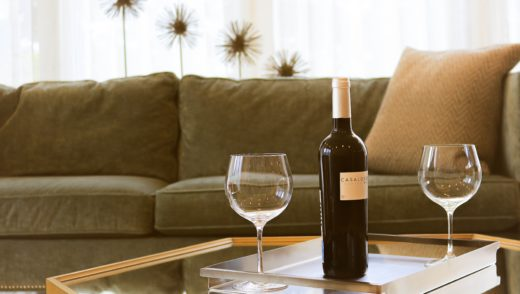 living room with two wine glasses and wine bottle on coffee table