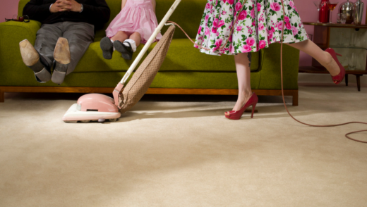 1950's Housewife vacuuming with husband in child on couch