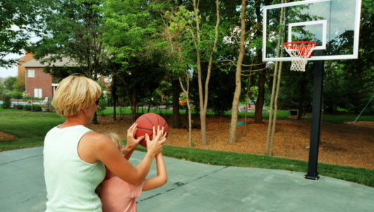 mom helping daughter learn to shoot a basketball