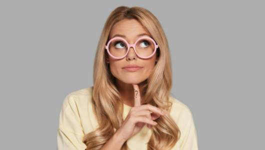 woman in glasses with finger under chin, finger has a question mark