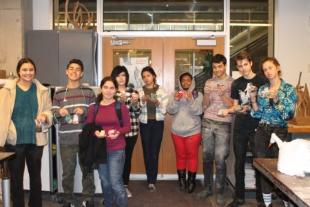 Students posing with booties they made for the exhibit