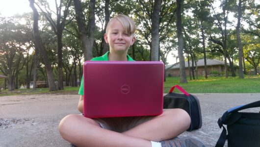Young boy smiling with computer in pink case