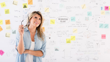 Creative woman thinking about a business plan with a wall chart at the background