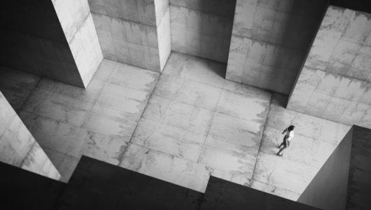 woman standing between tall walls of maze