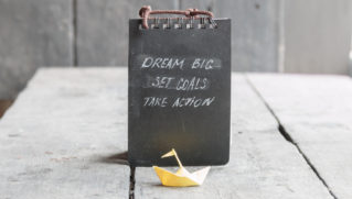 Dream Big - Set Goal - Take Action, handwriting on notebook cover, and a paper boat on an old table