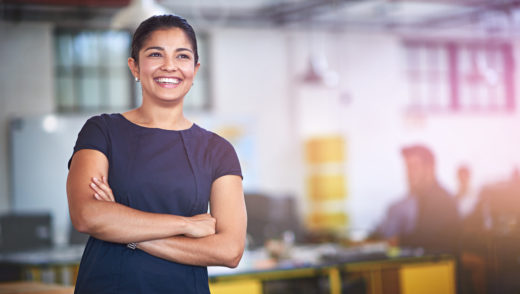 Shot of an attractive young businesswoman standing with her arms folded in the office