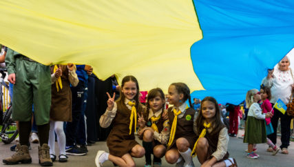 Little girls scouts sit under a flag