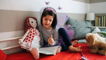 Little girl dressed as a butterfly sitting on the bed teaching her doll to read