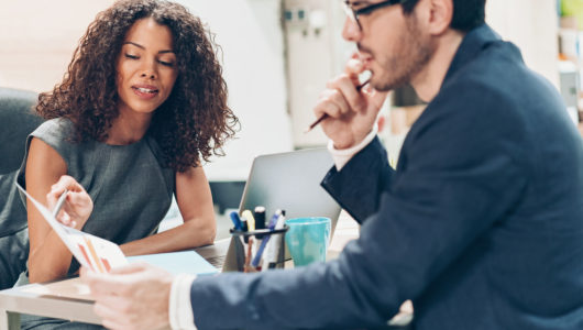 Businesswoman providing feedback on chart to male employee