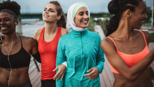 Multi ethnic group of young women exercise outdoor, next to the river. They are wearing sport clothing.