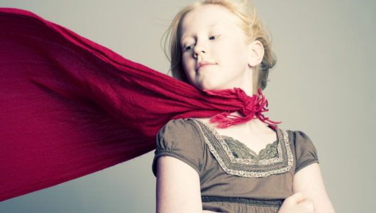Little Girl with red cape looking back over right shoulder