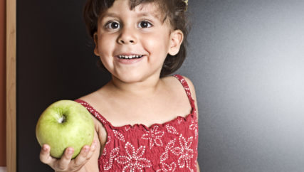 Smiling little girl holding an apple.