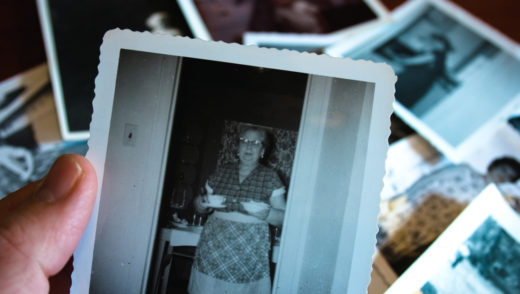 Hand holds vintage photograph of female with pile of old photos in background.