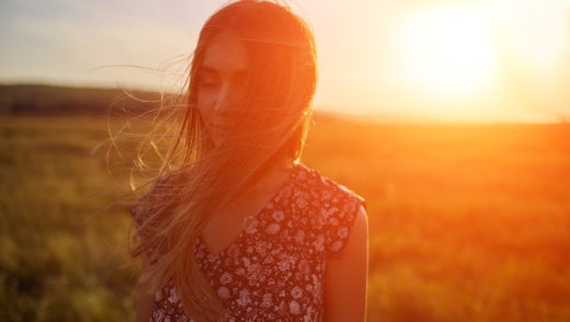 Beautyful girl outdoors enjoying nature. Resting on the field. Glow sun. Free happy woman. Toned in warm colors. Summer
