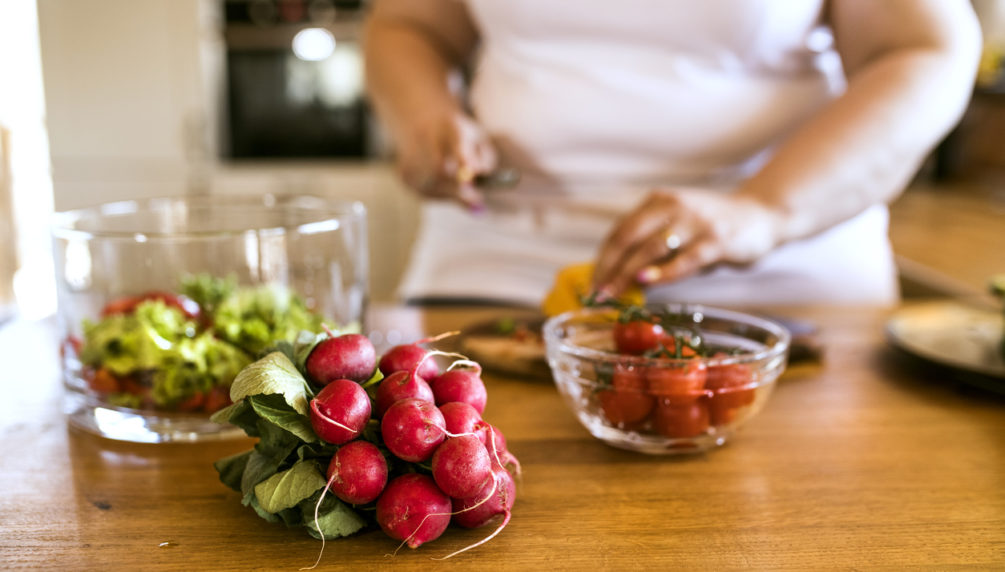 Unrecognizable overweight woman in white t-shirt at home preparing a delicious healthy vegetable salad in her kitchen.