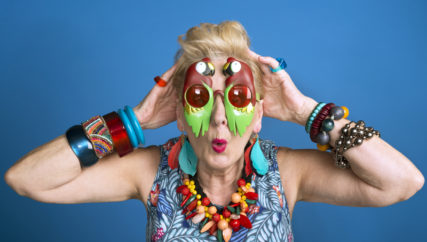 Summer portrait of creative, colorful senior woman wearing funny sunglasses. Studio shot.