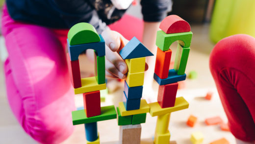 child playing with colorful wooden blocks