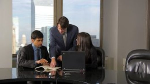 Two men and one woman in conference room