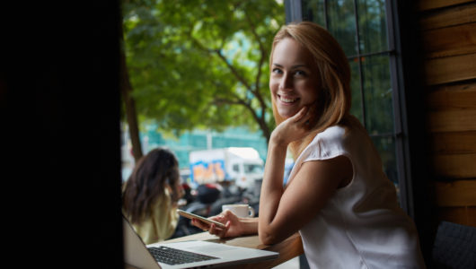 female posing while holding mobile phone after working on laptop computer while sitting